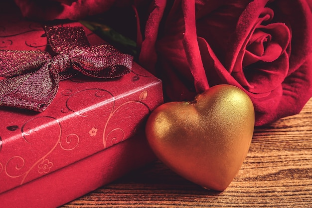 Goldherz mit geschenkbox und rotrose auf hölzernem hintergrund.