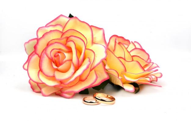 Goldhochzeit verlobungsringe mit gelben rosen blüht auf einem weißen hintergrund