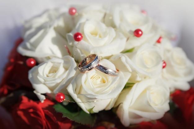 Goldhochzeitsringe auf einem blumenstrauß von beige rosen