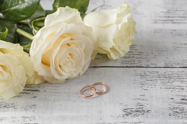Goldhochzeitsringe auf einem blumenstrauß von weißen rosen