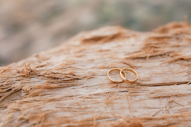 Goldhochzeitsringe auf einem unscharfen rauen hölzernen beschaffenheitshintergrund