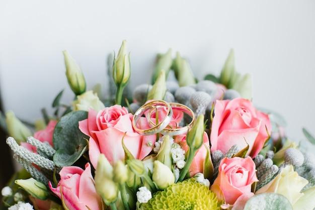 Goldhochzeitsringe liegen auf dem hochzeitsblumenstrauß der braut von rosen