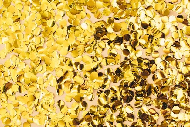 Goldkonfetti auf beige papierhintergrund. festliche urlaubskulisse. herzlichen glückwunsch zum geburtstag weihnachten neujahr. flache lage, ansicht von oben, kopienraum.
