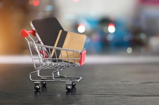 Goldkreditkarte und smartphone im kleinen einkaufswagen begrifflich vom interneteinkaufen