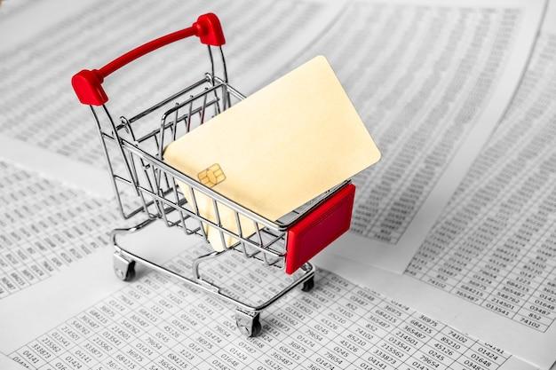 Goldkreditwagen im einkaufswagen und in den finanzberichten. einkaufen, geschäftskonzept. zahlung