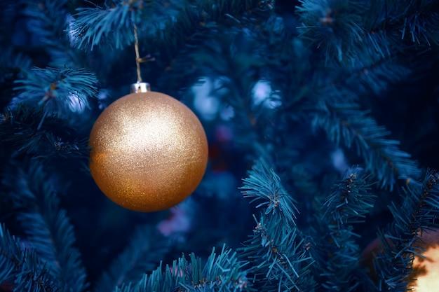 Goldkugel auf neujahrsbaum. weihnachtsdekoration für den urlaub.