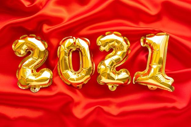 Goldluftfolienballons in form der nummern 2021 auf rotem stoff