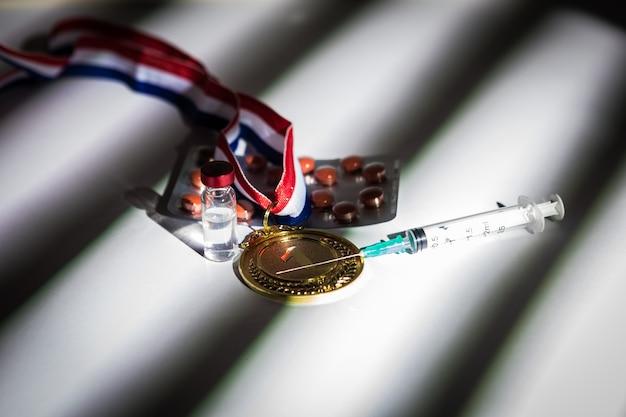 Goldmedaille des meisters, spritze mit dopingmittel, tablettentablette und durchstechflasche mit verbotener substanz mit licht und schatten, die durch das fenster kommen. sport- und dopingkonzept