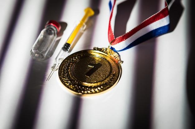 Goldmedaille des meisters, spritze mit dopingsubstanz und fläschchen mit verbotener substanz mit licht und schatten durch das fenster. sport- und dopingkonzept