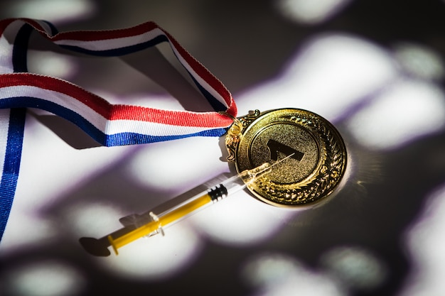 Goldmedaille des meisters und spritze mit dopingsubstanz mit licht und schatten, die durch das fenster kommen. sport- und dopingkonzept