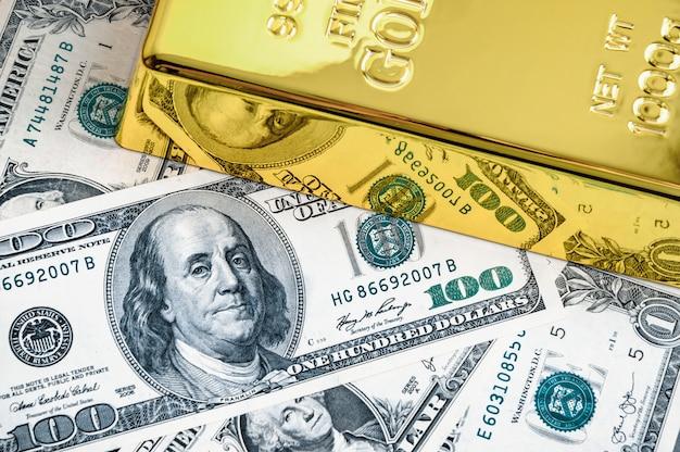 Goldmetallbarrenbarren auf dem hintergrund von dollarscheinen.