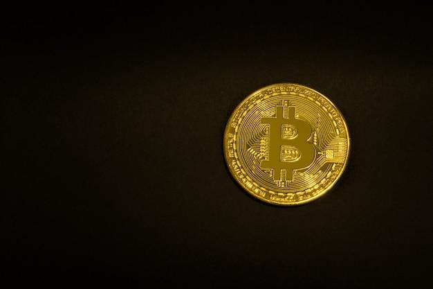 Goldmünze bitcoin auf einem schwarzen hintergrund. isolieren. platz für text