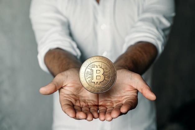 Goldmünze bitcoin in der hand