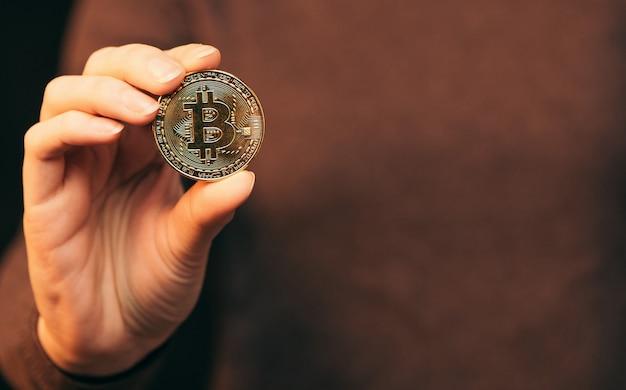 Goldmünze bitcoin kryptowährung. das symbol der kryptowährung in der hand halten.