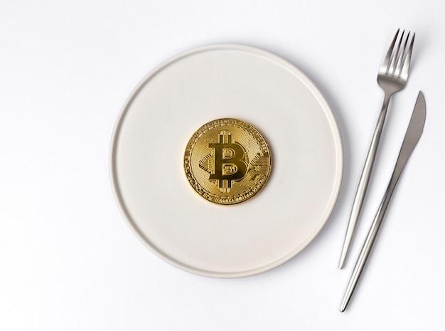 Goldmünze bitcoin serviert auf weißem leeren teller