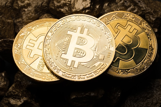 Goldmünze bitkoyn und ein hügel aus gold