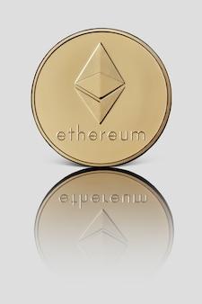 Goldmünze ethereum. die vorderseite der münze spiegelt sich auf einer weiß glänzenden oberfläche wider. kryptowährung und blockchain-konzept.