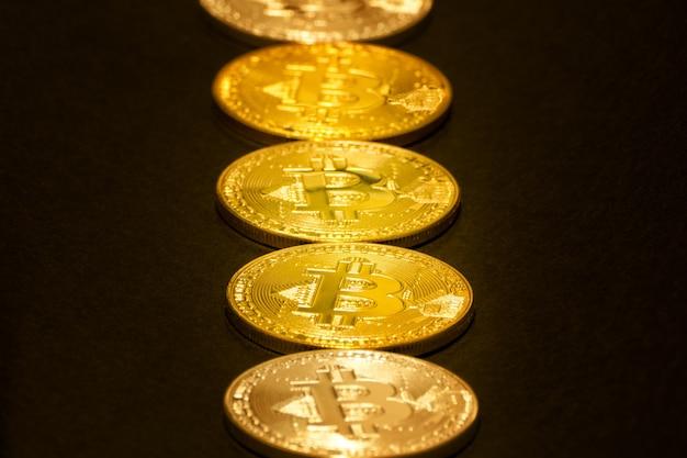 Goldmünzen bitcoin liegen in einer reihe. schwarzer hintergrund