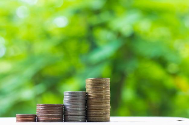 Goldmünzen stehen vertikal in spalten auf naturhintergrund. konzept des umsatzwachstums