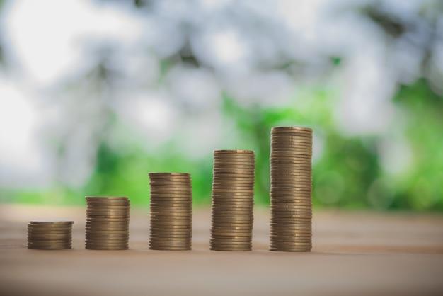 Goldmünzen und anlage mit grünem bokeh beleuchten beim einsparen des geldkonzeptes