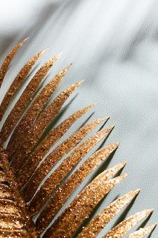 Goldpalmenblätter und -schatten auf einem blauen wandhintergrund.