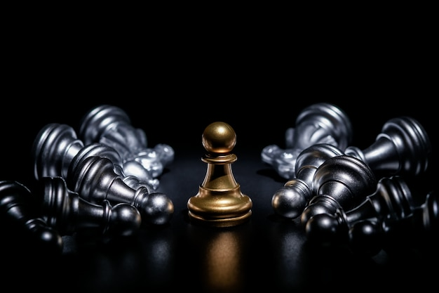 Goldpfandschach umgeben durch einige gefallene silberne schachfiguren, geschäftsstrategiekonzept