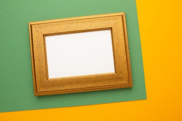 Goldrahmen auf grünem und orangefarbenem hintergrund mit platz für ihren text. foto in hoher qualität