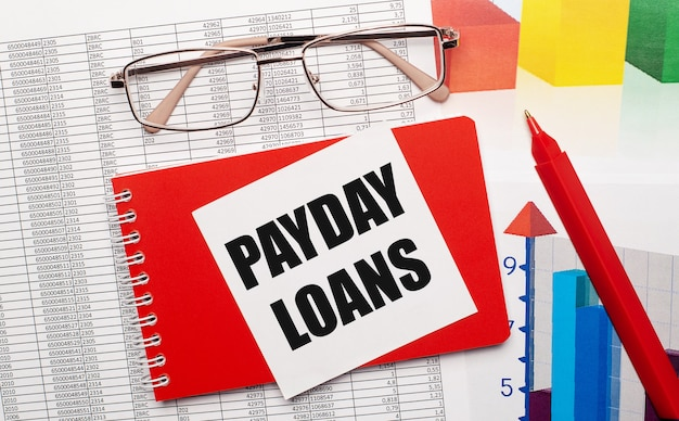 Goldrandbrille, ein roter stift, farbtabellen und ein rotes notizbuch mit einer weißen karte mit dem text payday loans auf dem desktop