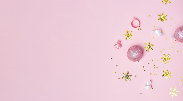 Goldrosa und weiße weihnachtsdekorationen auf rosa hintergrund. weihnachten neujahr oder partybanner