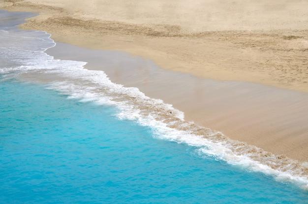 Goldsandstrand mit türkisfarbenen meereswellen. sommerzeit und feiertagskonzepthintergrund. abstrakter seestückhintergrund. draufsicht. platz für text.