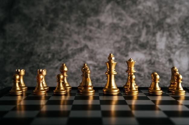 Goldschach auf schachbrettspiel für geschäftsmetapher-führungskonzept