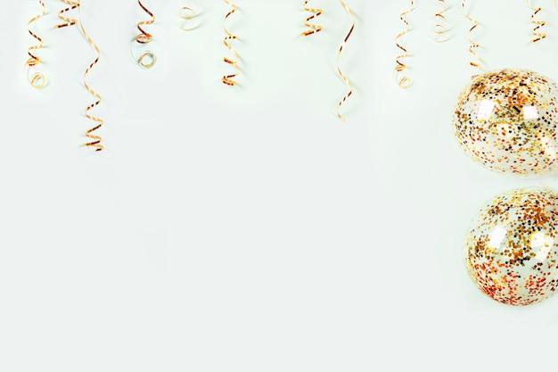 Goldschlangen-feiertagsdekoration und luftballons mit buntem konfetti auf hellem hintergrund