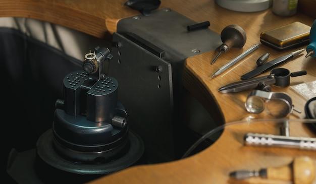 Goldschmied bei der arbeit. werkbank des juweliers mit verschiedenen werkzeugen. desktop zum basteln von schmuck mit professionellen werkzeugen.