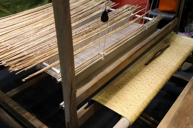Goldseide auf webstuhl, baumwolle auf manuellem holzwebstuhl in asien