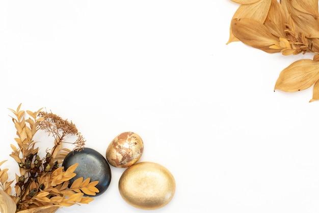 Goldsteine und trockenblumen auf einem weißen hintergrund. badekurorthintergrund und goldblatt