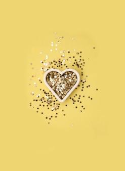 Goldstern funkelt form des herzens auf gelber oberfläche, valentinstagspartykonzept