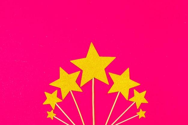 Goldsterndekoration auf rosa hintergrund