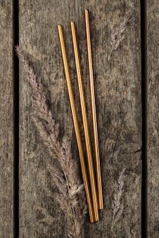 Goldstrohhalme aus rostfreiem metall auf hölzernem hintergrund
