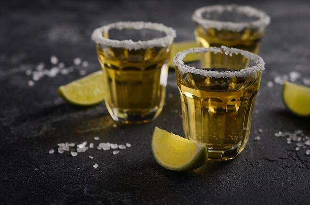 Goldtequila mit limetten- und salzrand auf dunklem stein