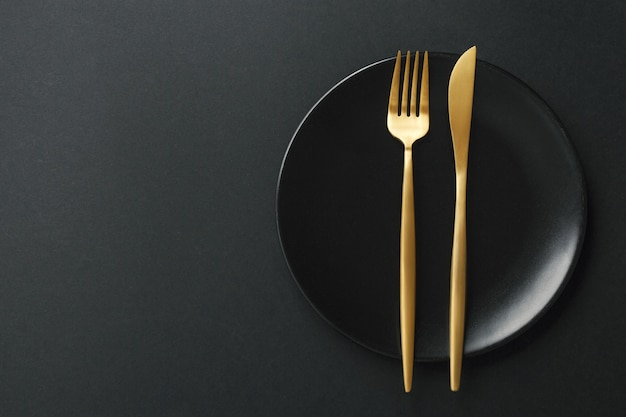 Goldtischbesteck eingestellt auf schwarzen hintergrund