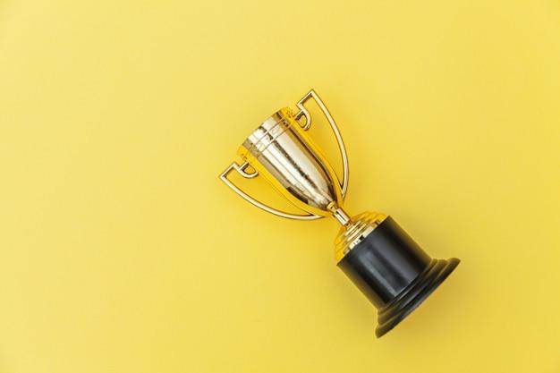 Goldtrophäenbecher des gewinners oder des meisters lokalisiert auf gelbem buntem hintergrund