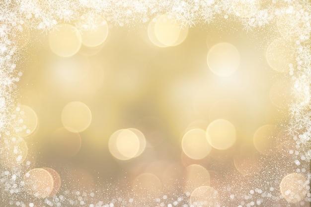 Goldweihnachtshintergrund mit schneebedeckter grenze