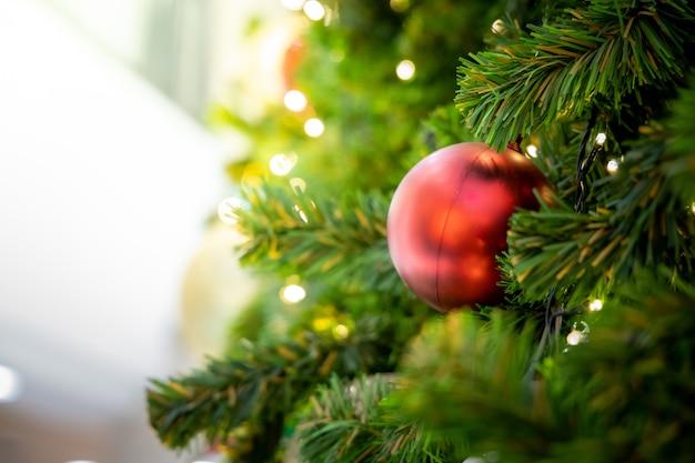 Goldweihnachtshintergrund von de-fokussierten lichtern mit verziertem baum