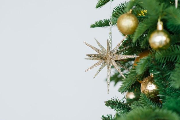 Goldweihnachtshintergrund von defokussierten lichtern mit geschmücktem baum