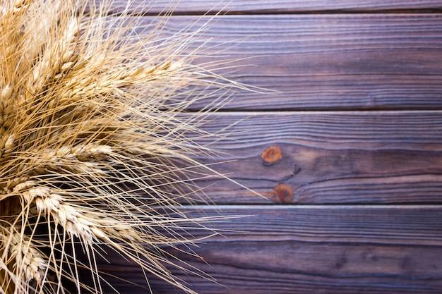 Goldweizen, der auf einer braunen holzoberfläche liegt