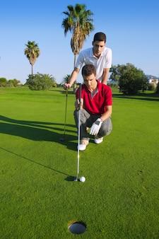 Golf junger mann, der das loch schaut und zielt