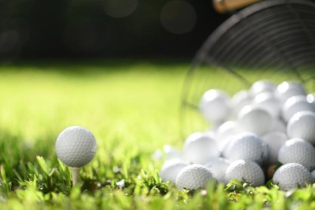 Golfball auf abschlag und golfbälle im korb auf grünem gras zum üben