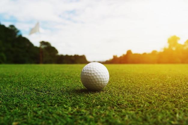 Golfball auf grünem gras mit loch und sonnenlicht