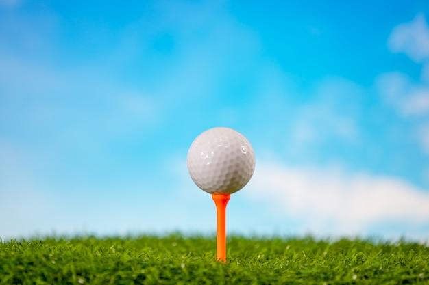 Golfball auf t-stück im golfplatz auf blauem himmel
