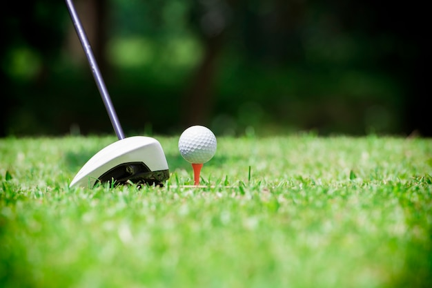 Golfball auf t-stück vor golffahrer auf einem golfplatzgrasgrünfeld